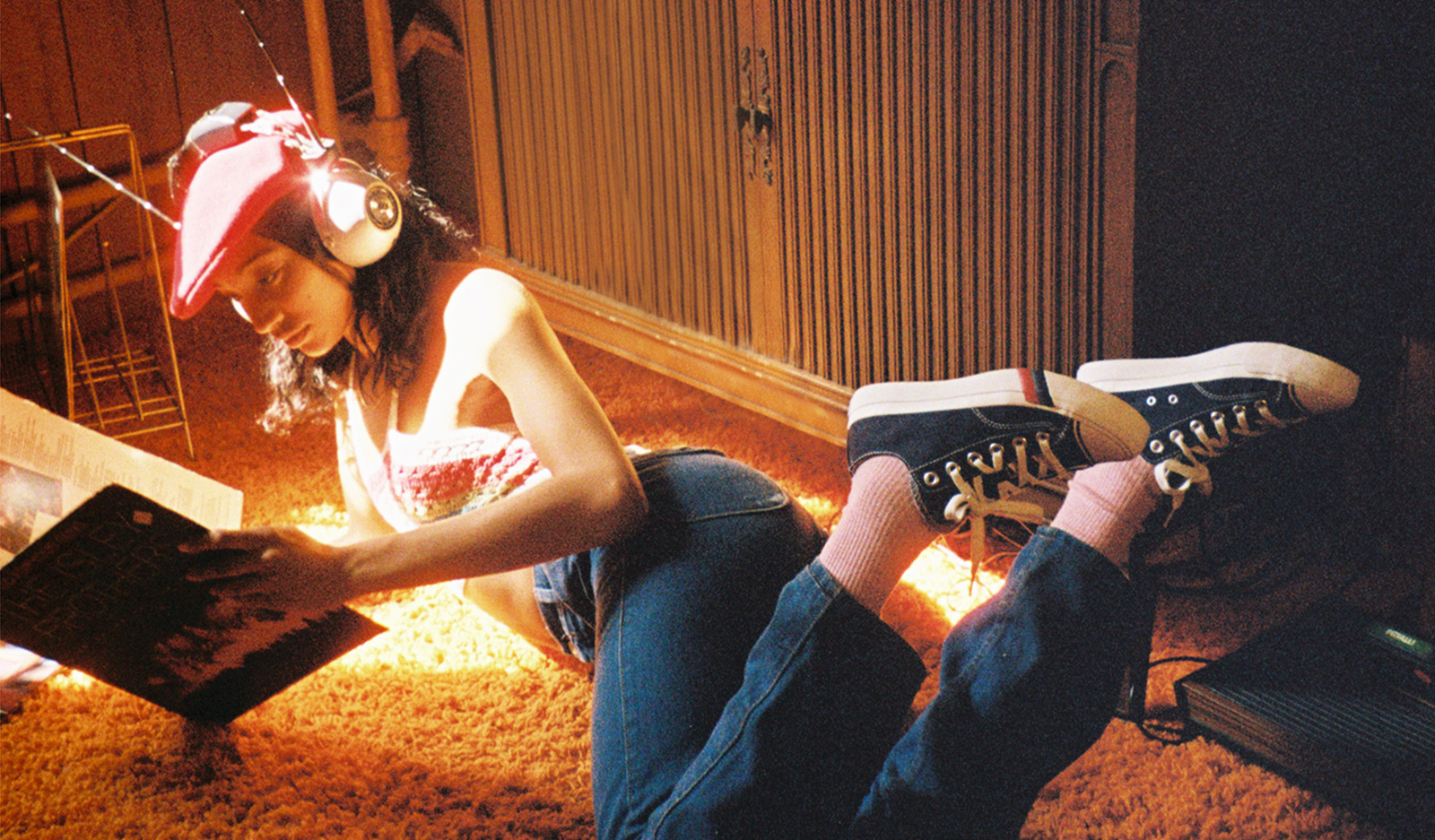 A female grooving to the tunes in her headphones, while chilling on the floor, wearing a pair of ProKeds on her feet.