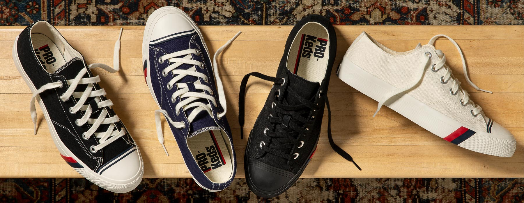 Four Pro-Keds shoes in a variety of colors sitting on a wooden bench.