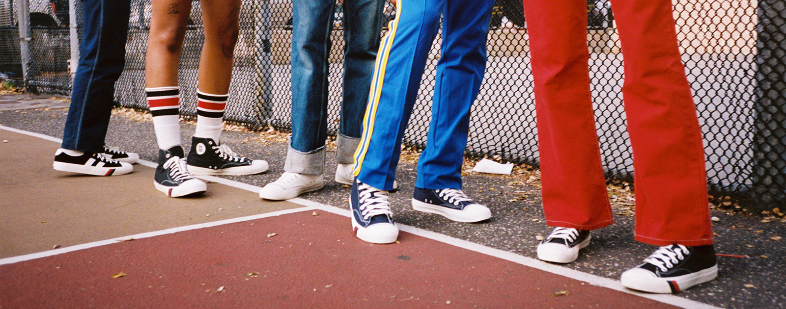 Group of friends along a fence on a basketball court, wearing ProKeds.