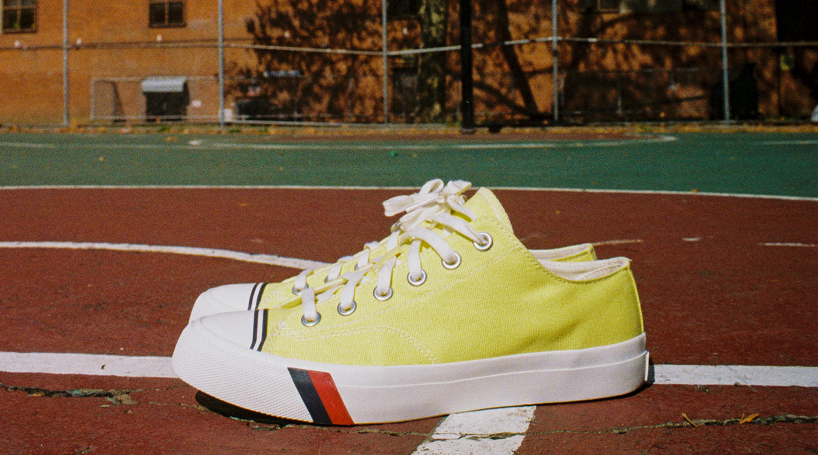 Pair of Pro-Keds Royal Lo's in yellow on a city basketball court.