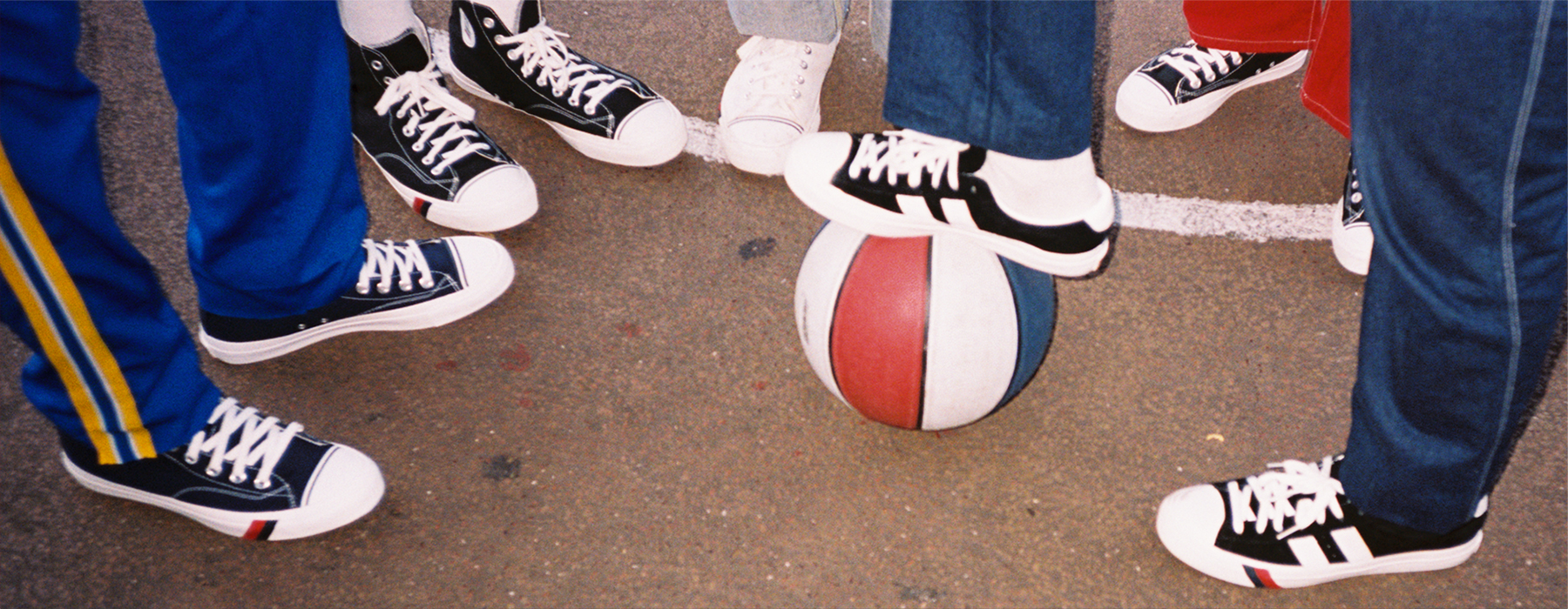 A group of people surrounding a patriotic basketball all wearing pro keds.